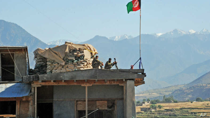 FILE - two Afghan soldiers sit on a guard tower at a military base in Nari district, Kunar province, Afghanistan.