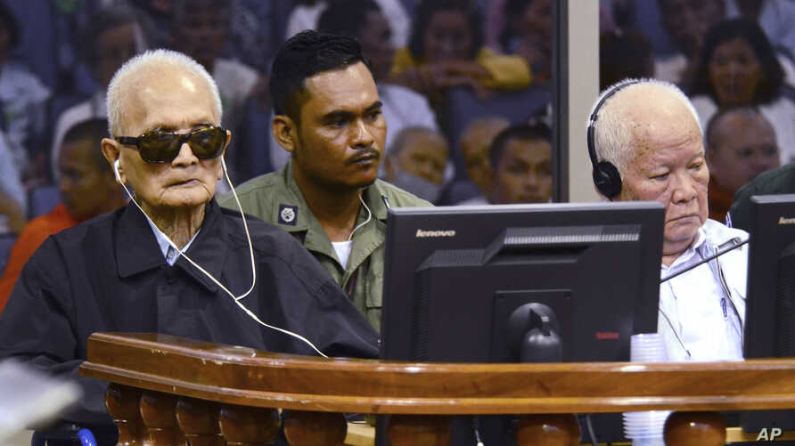In this photo released by the Extraordinary Chambers in the Courts of Cambodia, the two most senior surviving members of the Khmer Rouge regime Nuon Chea, left, and Khieu Samphan listen to the verdict which upheld their life sentences in Cambodia's t...