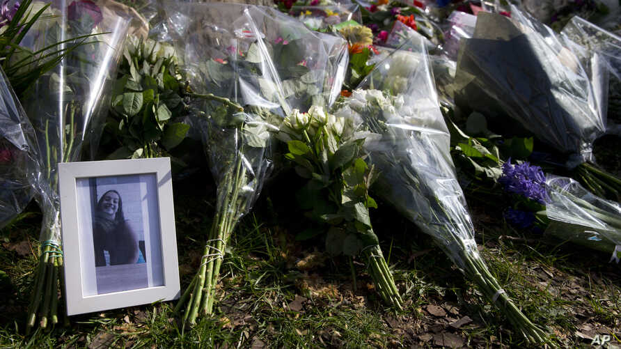 A picture of one of the three victims sits amidst flowers as mourners pay their respect at the site of a shooting incident in a tram in Utrecht, Netherlands, March 19, 2019.