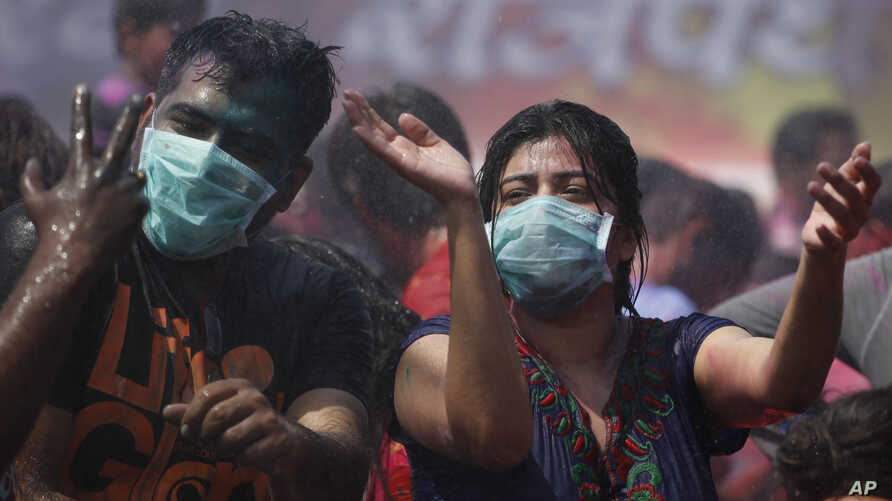Indians, wearing masks on their faces as preventive measure for swine flu, dance in artificial rain as they celebrate Holi in Ahmadabad, India, March 6, 2015.