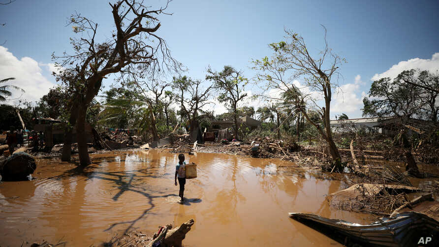 A child walks past debris as flood waters begin to recede in the aftermath of Cyclone Idai, in Buzi near Beira, Mozambique, March 24, 2019.