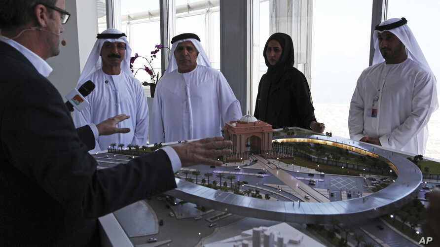 FILE - Rob Lloyd, the CEO of Hyperloop One, left, shows a model to Emirati officials including Mattar al-Tayer, the director-general and chairman of Dubai's Roads & Transport Authority, third left, in Dubai, United Arab Emirates, Nov. 8, 2016.