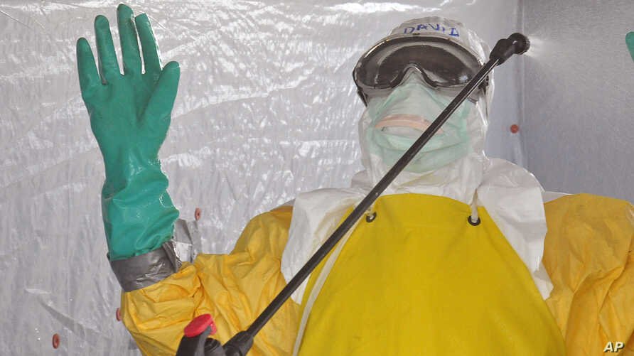 A health worker is sprayed with disinfectant after he worked with patients that contracted the Ebola virus, at a clinic  in Monrovia, Liberia, Monday, Sept. 8, 2014.  Border closures, flight bans and mass quarantines are creating a sense of siege in ...