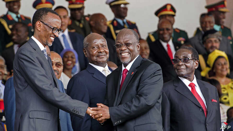 Tanzania's newly elected president John Magufuli (2ndR) shakes hands with Rwanda's president Paul Kagame (L) eyed by Zimbabwe's president Robert Mugabe (R) and Uganda's president Yoweri Museveni (2ndL) during the swearing in ceremony in Dar es Salaam
