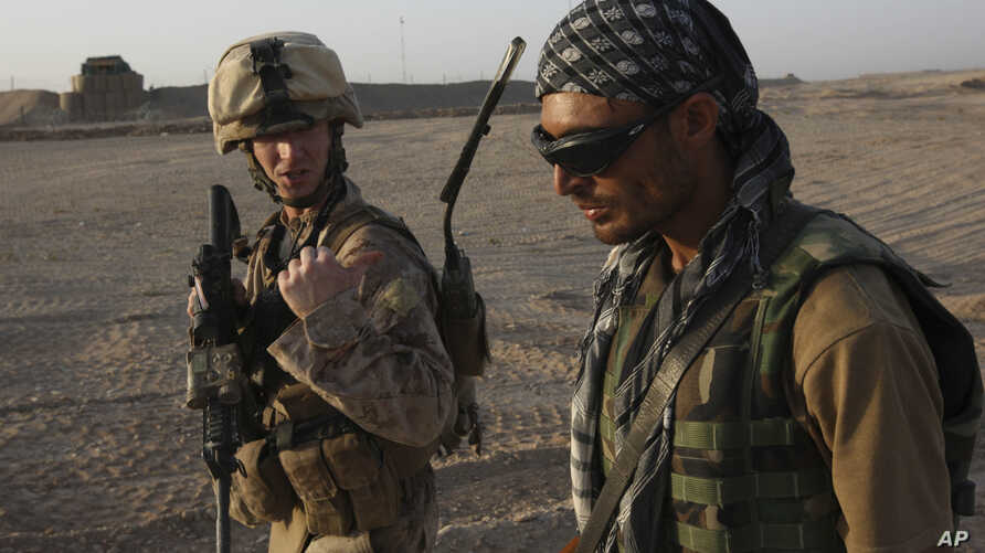 FILE - U.S. Marine 1st Lt. Zachary Bennett talks with Afghan interpreter during a joint patrol in Helmand province, southern Afghanistan, Sept. 19, 2009. The Special Immigrant Visa (SIV) program, created in 2008, allows Afghan interpreters to immigra