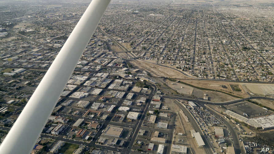 FILE - This May 1, 2015 photo shows an aerial view of the US Mexico border showing Calexico, Calif. below and Mexicali, Mexico above.