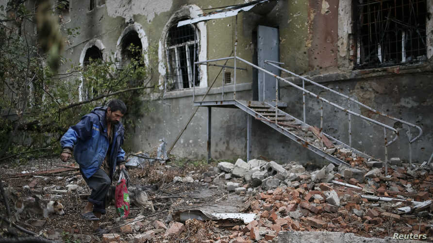 A local resident walks past buildings damaged by recent shelling in the eastern Ukrainian village of Semenovka July 9, 2014.