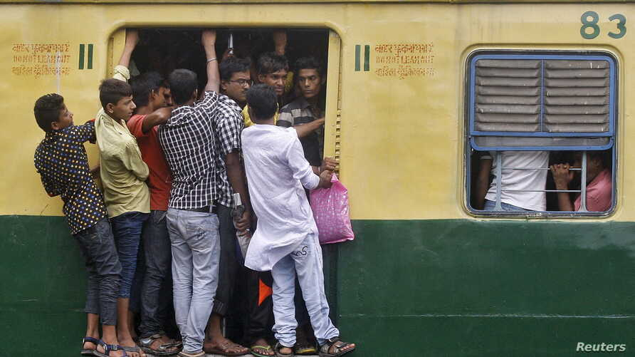 FILE - Commuters stand at an open doorway of a suburban train during the morning rush hour in Kolkata, India, July 31, 2015. India is set to overtake China and become the world's most populous country in less than a decade - six years sooner than pre