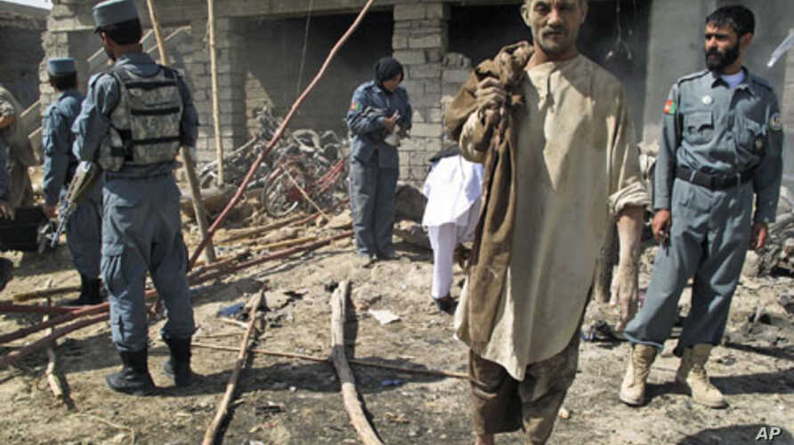 Police officers inspect the site of a suicide car bomb attack as a survivor leaves the scene, in Helmand province, Afghanistan, September 27, 2011.