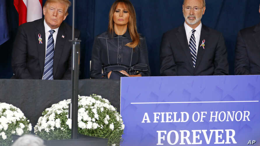 President Donald Trump, left and first lady Melania Trump, center, and Pennsylvania Governor Tom Wolf, listen as the names of the 44 people who died in the crash of Flight 93 are read during the September 11th Flight 93 Memorial Service in Shanksvill