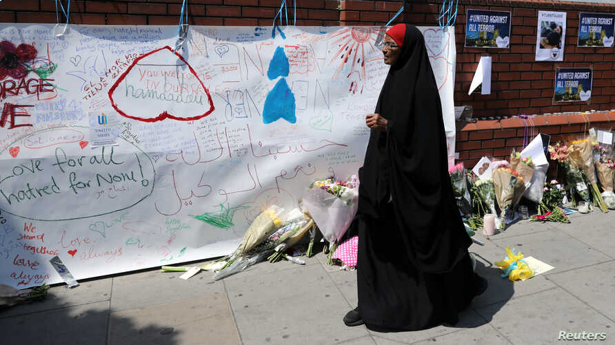 A woman walks past messages attached to a wall near the scene of an attack next to Finsbury Park Mosque, in north London, June 20, 2017.