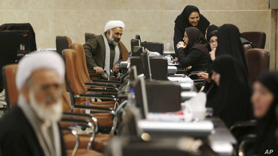 An Iranian cleric speaks with  election staff while registering his candidacy for the February 26 Experts Assembly elections at the Interior Ministry in Tehran, Iran, Dec. 17, 2015.