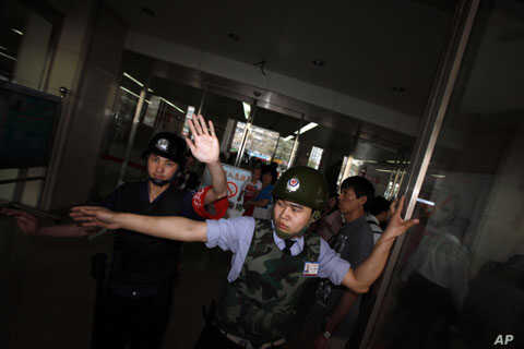 Chinese security guards block journalists at the entrance of a hospital where blind activist lawyer Chen Guangcheng is recuperating in Beijing,  May 4, 2012.