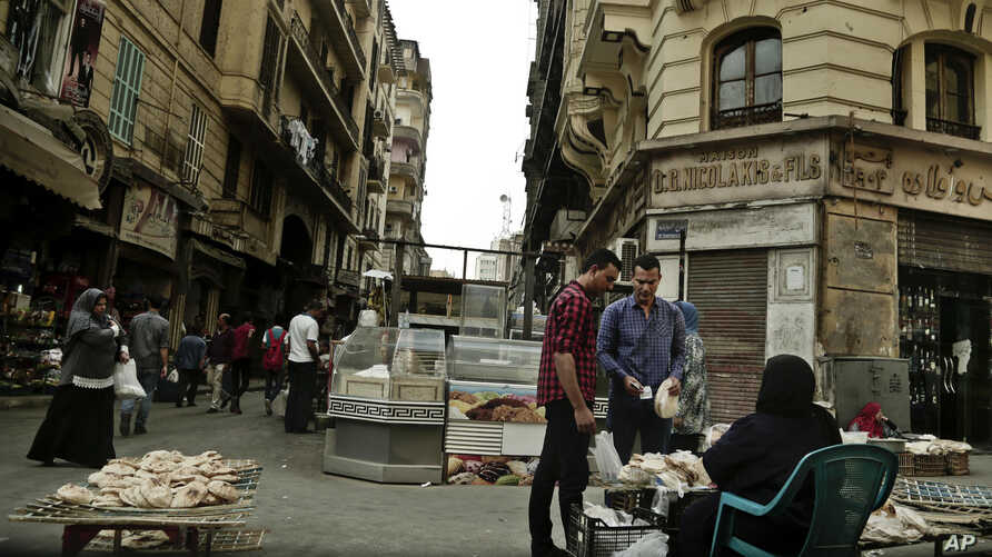 FILE -- A woman sells bread near the Tawfiqia market in downtown Cairo, Egypt, Oct. 18, 2016. Shortages and rising food prices are feeding discontent among Egyptians, who are also enduring new taxes and a hike in utility bills.