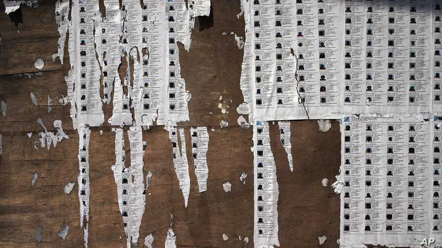 Torn voter's lists are seen outside the St. Raphael school in the Limete district of Kinshasa, Monday Dec. 31, 2018. Forty million voters were registered for a presidential race plagued by years of delay and persistent rumors of lack of preparation.