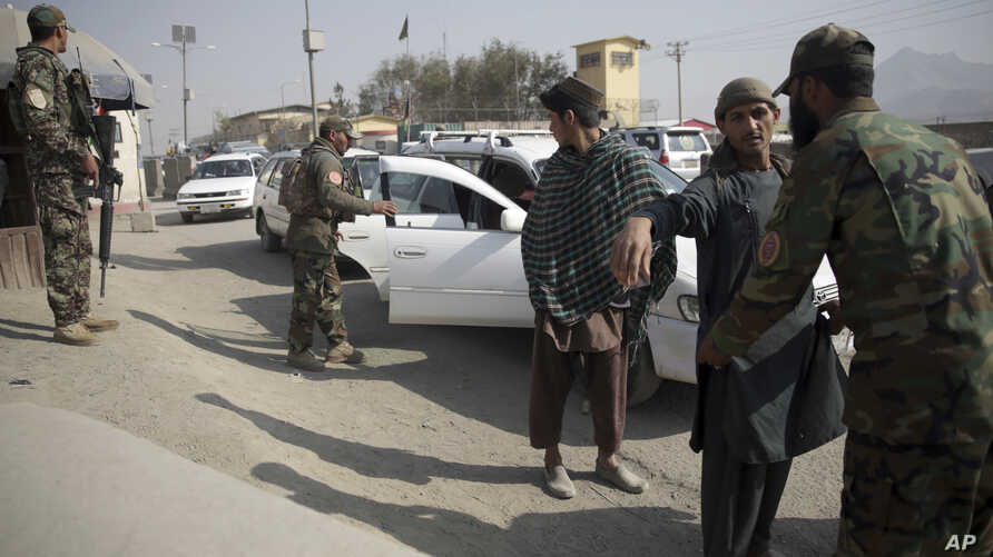 FILE - Afghan National Security Forces search passengers and vehicles at a checkpoint in Kabul, Afghanistan, Oct. 26, 2018.