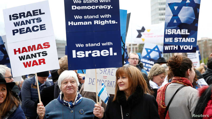 "People hold placards during the ""Rally for Equal Rights at the United Nations (protesting Anti-Israeli bias)"" aside of the Human Rights Council at the United Nations in Geneva, Switzerland, March 18, 2019."