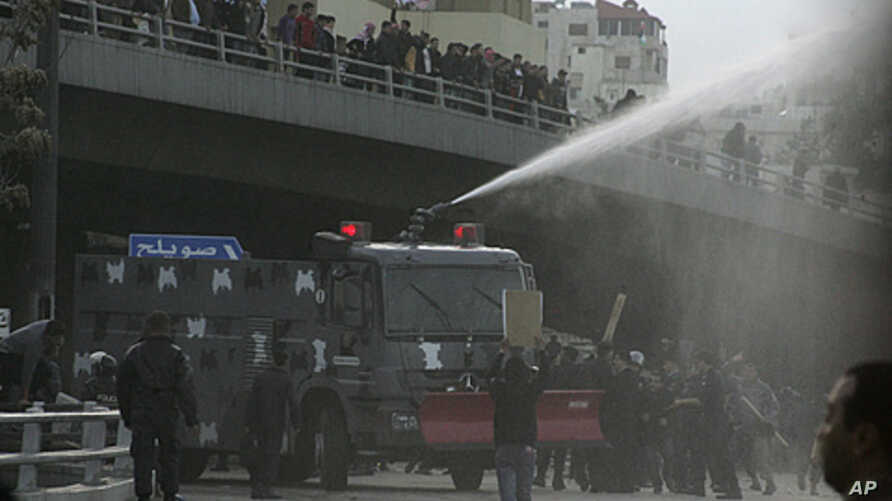 "Protesters calling themselves the ""Youth of March 24 Movement"" demonstrate to demand for political reform and the ouster of the prime minister in front of police water canons at a main square in Amman, March 25, 2011"