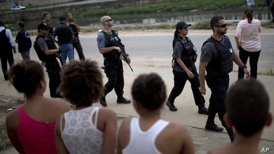 In this April 12, 2017 photo, police patrol an area near the school where a 13-year-old girl was shot and killed at a school in Acari, a poor northern neighborhood in Rio de Janeiro.