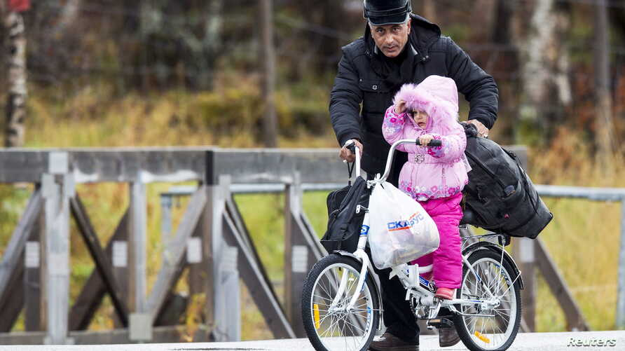 A man pushes a girl across the border from Russia to Norway on a bicycle with flat tires at the Storskog border station in northern Norway, Oct. 13, 2015. Migrants entering Norway via Russia must travel by bicycle to comply with a Russian law barring