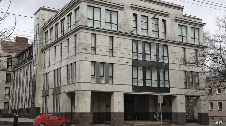 """FILE - A women enters the four-story building known as the """"troll factory""""  in St. Petersburg, Russia. The """"troll factory"""" is where hundreds of young Russians work around the clock writing blogs and posting comments on the Internet staunchly supporti"""