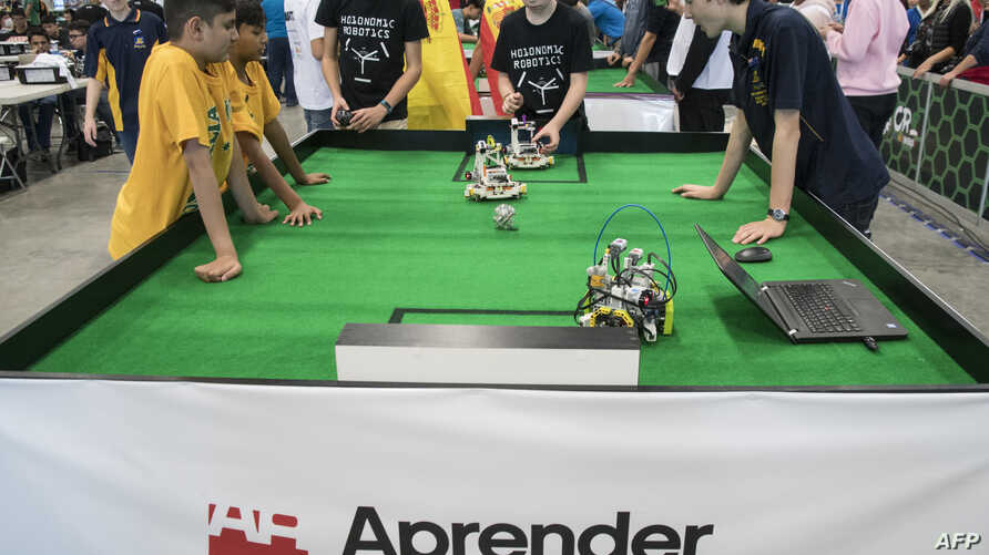 Miniature robots play soccer as participants look on during the World Robotics Olympiad at a convention center in San Rafael, Alajuela, Costa Rica, Nov. 10, 2017. This year's edition is the first taking place in Latin America.