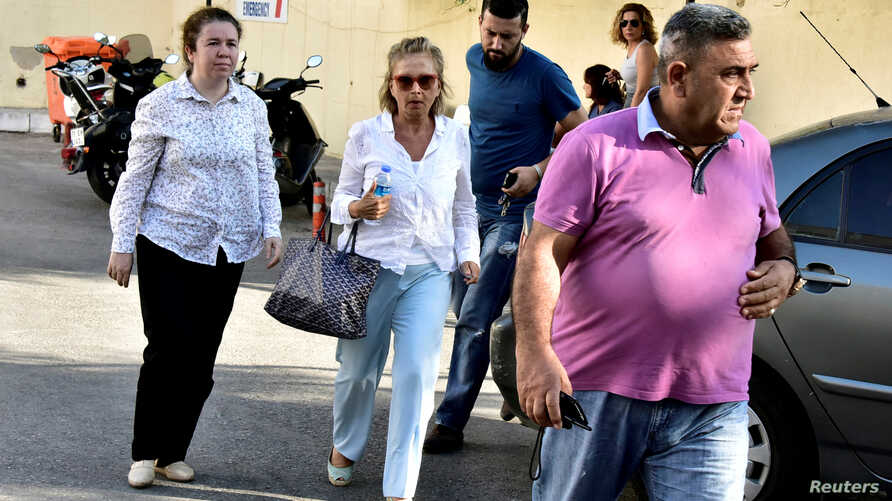 Turkish journalist Nazli Ilicak (C), also a well-known commentator and former parliamentarian, is escorted by a police officer (R) and her relatives (L and rear) after being detained and brought to a hospital for a medical check in Bodrum, Turkey, Ju