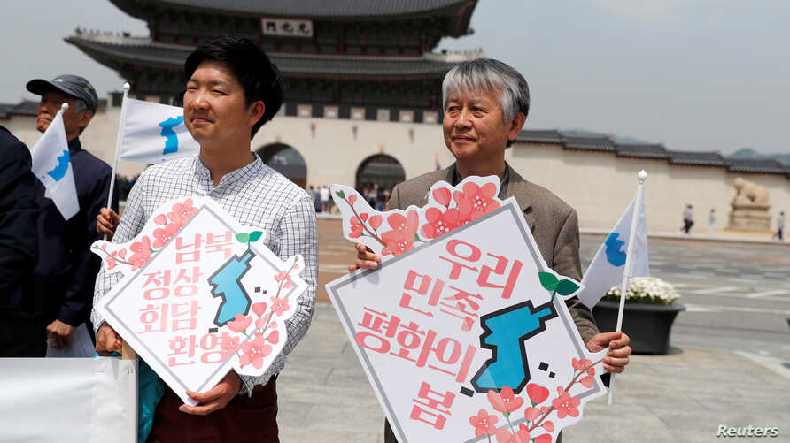 "People hold Korean Unification Flags during a pro-unification rally ahead of the upcoming summit between North and South Korea in Seoul, Apr. 26, 2018. The signs read, ""Welcome inter-Korean summit"" (L) and ""Peaceful spring for our people"" (R)."