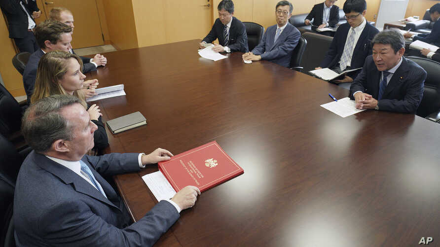 FILE - Britain's Secretary of State for International Trade Liam Fox, bottom left, and Japanese Minister of Economic Revitalization Toshimitsu Motegi, right, attend a meeting in Tokyo July 31, 2018.
