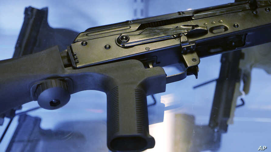 """FILE - A little-known device called a """"bump stock"""" is attached to a semi-automatic rifle at the Gun Vault store and shooting range, in South Jordan, Utah, Oct. 4, 2017. The device was used by Las Vegas shooter Stephen Paddock."""