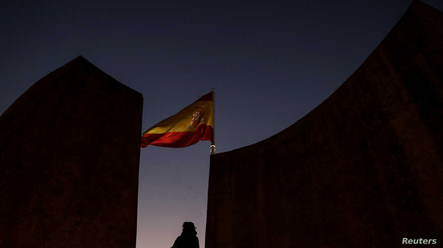 A woman stands near a Spanish flag in Plaza Colon (Columbus Square) on the eve of regional elections in Catalonia in Madrid, Dec. 20, 2017.