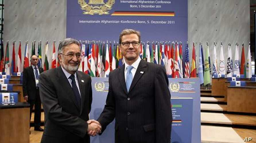 German Foreign Minister Guido Westerwelle, right, and his Afghan counterpart Salmai Rassul shake hands as they visit the World Conference Centre Bonn (WCCB) , Germany, December 3, 2011.
