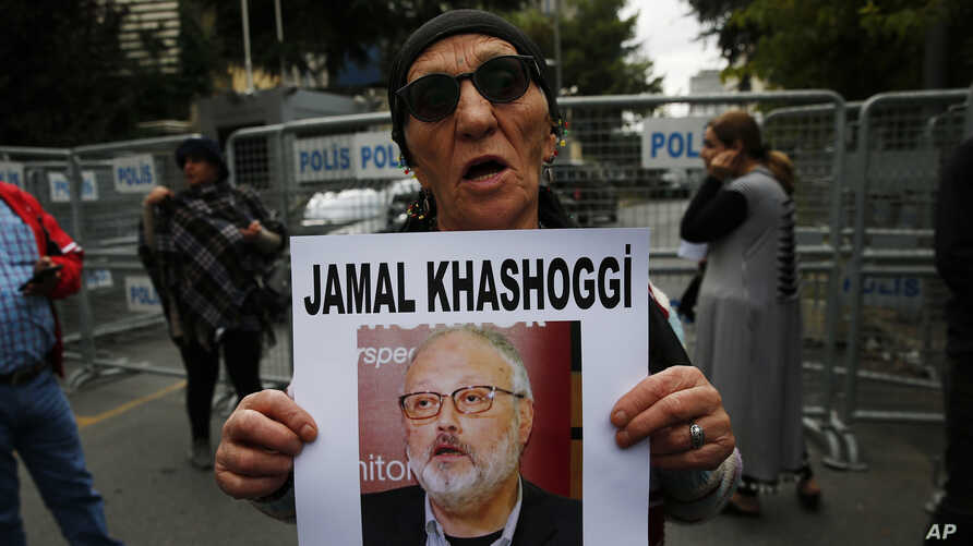 A member of the Human Rights Association Istanbul branch, holds a poster with a photo of missing Saudi journalist Jamal Khashoggi, during a protest in his support near the Saudi Arabia consulate in Istanbul, Oct. 9, 2018.