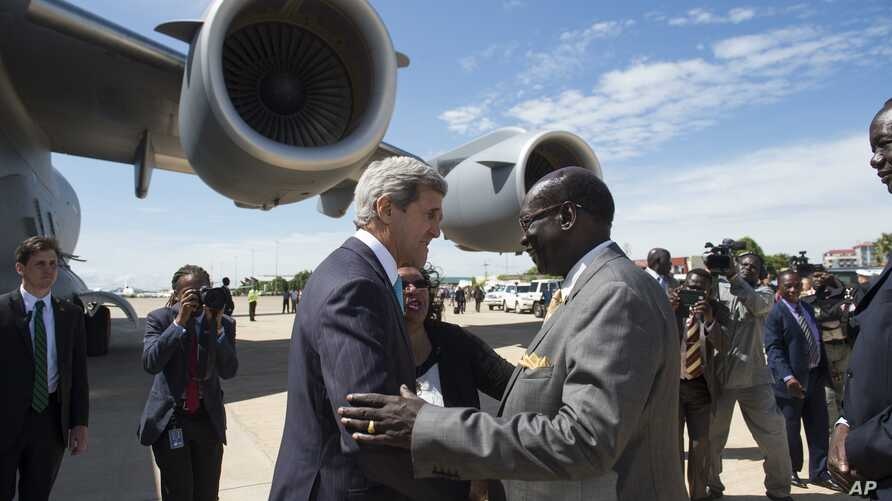 South Sudanese Foreign Minister Barnaba Marial Benjamin, right, welcomes US Secretary of State John Kerry upon his arrival at Juba International Airport, South Sudan, Friday May 2, 2014. Kerry, landing in the capital Juba on Friday, carried the threa