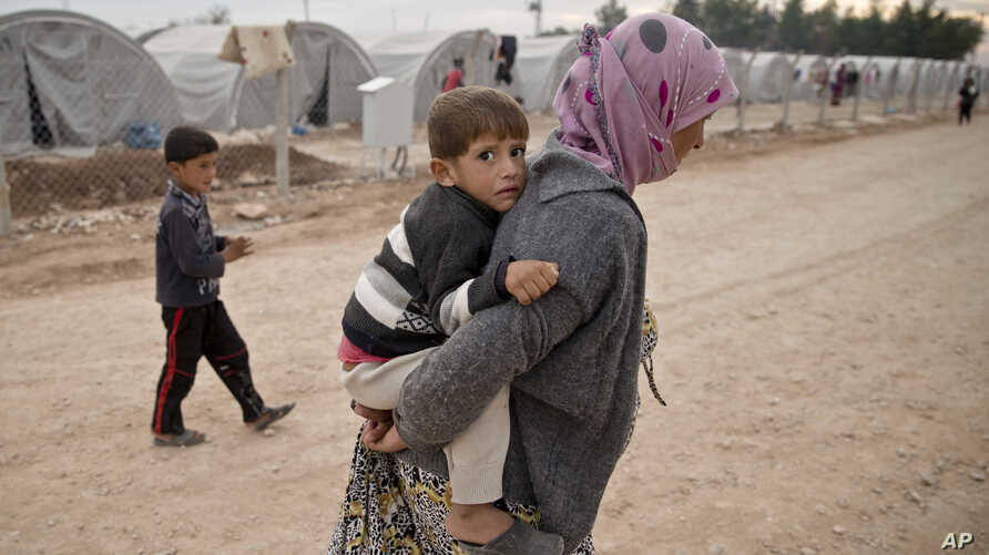 A Syrian Kurdish refugee woman from Kobani, carries a baby at a refugee camp in Suruc, near the Turkey-Syria border, Thursday, Oct. 23, 2014. Kobani, also known as Ayn Arab, and its surrounding areas, has been under assault by extremists of the Islam
