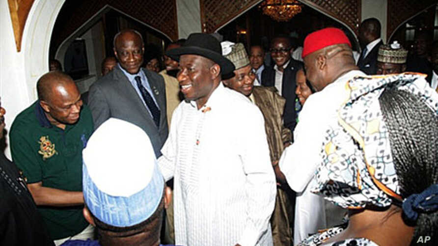 Nigerian President Goodluck Jonathan (C), accompanied by his running mate Arc Namadi Sambo, is congratulated by Cabinet members after being declared winner of the presidential election, in Abuja, on April 18, 2011
