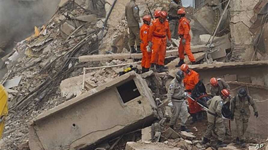 Rescue workers carry the body of a victim after a building collapsed in Rio de Janeiro, Brazil, Jan. 26, 2012.