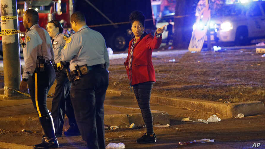 FILE - Police officers interview witnesses, Feb. 25, 2017, at the scene where a vehicle struck a crowd and other vehicles during the Krewe of Endymion parade in New Orleans. Saturday night a car struck a crowd on Esplanade Avenue, near the Endymion p