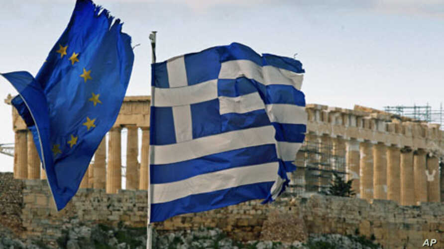 The Parthenon on the Athens Acropolis is seen behind a Greek and an EU flag atop the Greek ministry of finance, February 8, 2012.