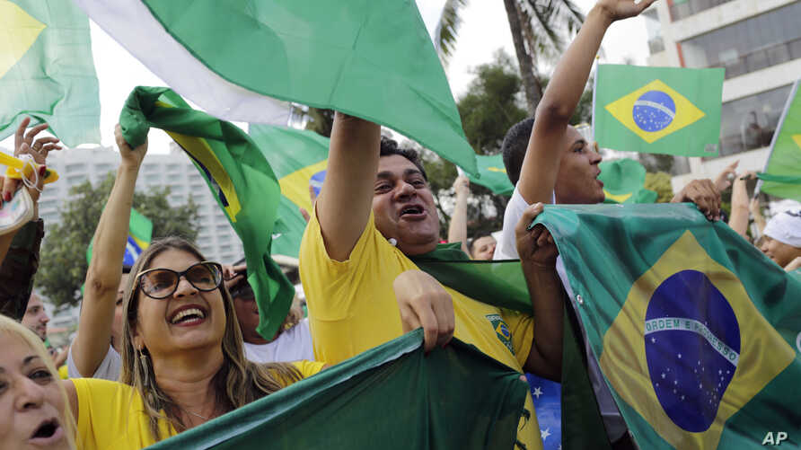 Supporters of Brazilian presidential candidate Jair Bolsonaro cheer as they gather outside his residence in Rio de Janeiro, Brazil, Sunday, Oct. 28, 2018, during the country's presidential runoff election.