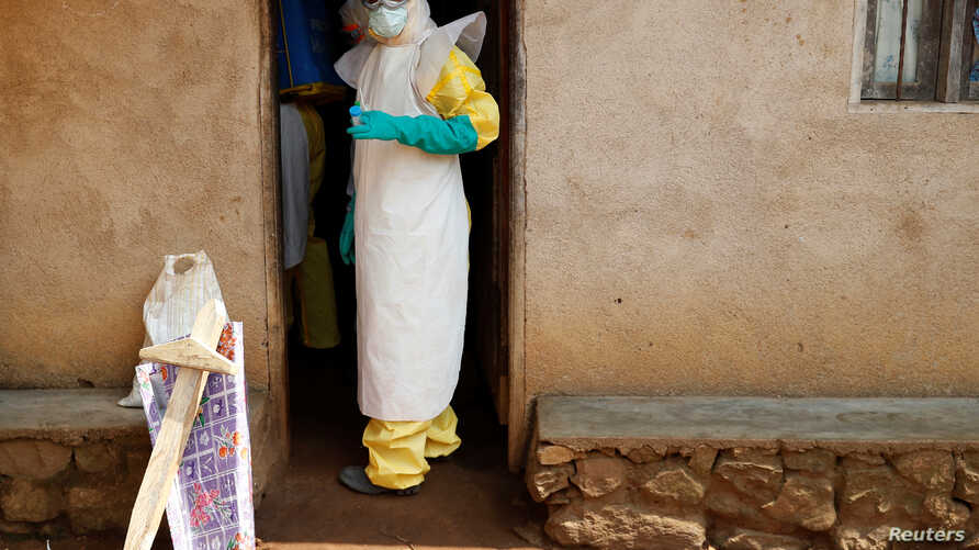 Health care workers enter a house where a baby suspected of dying of Ebola is, during the baby's funeral in Beni, North Kivu province, Democratic Republic of the Congo, Dec. 18, 2018.