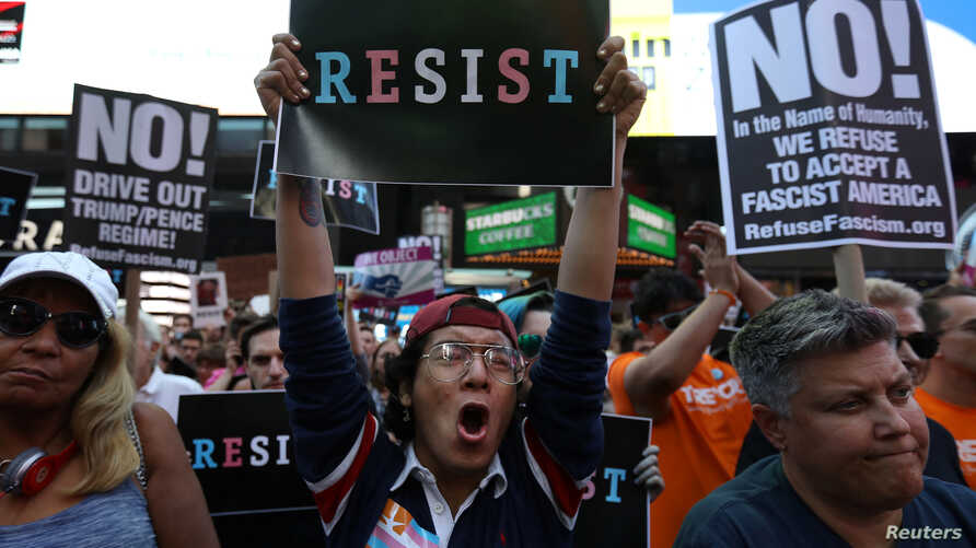 FILE - People protest U.S. President Donald Trump's announcement that he plans to reinstate a ban on transgender individuals from serving in any capacity in the U.S. military, in Times Square, in New York City, New York, U.S., July 26, 2017.