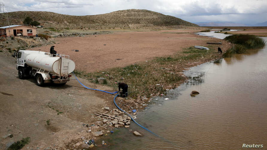 FILE - A water truck pomps water from Desaguadero river during the worst drought in 25 years near Oruro, Bolivia, Dec. 1, 2016.