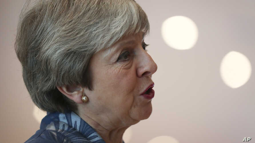 British Prime Minister Theresa May speaks with the media as she arrives for an EU-Arab summit at the Sharm El Sheikh convention center in Sharm El Sheikh, Egypt, Sunday, Feb. 24, 2019.