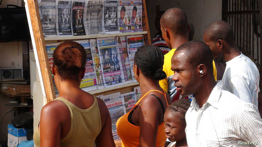 FILE - People read news headlines at a newsstand in Conakry, March 28, 2014.