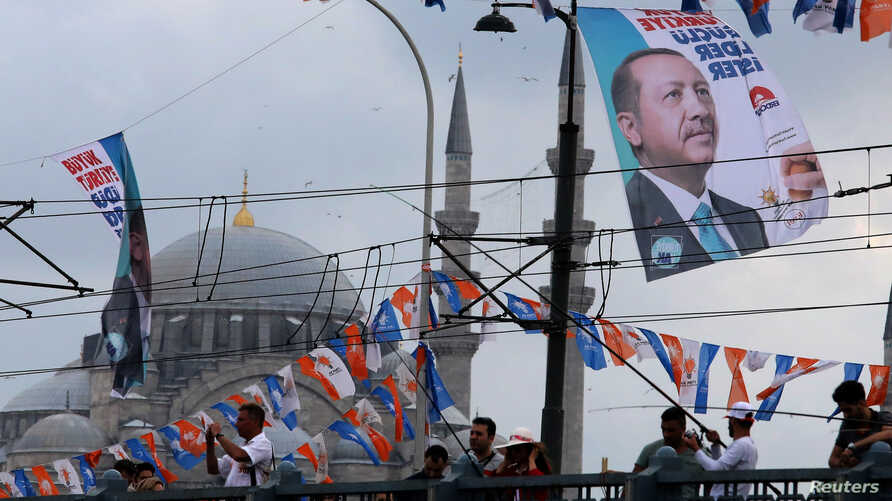 A banner of Turkish President Tayyip Erdogan and Turkey's ruling AK Party (AKP) flags hang over Galata bridge in Istanbul,, June 10, 2018.
