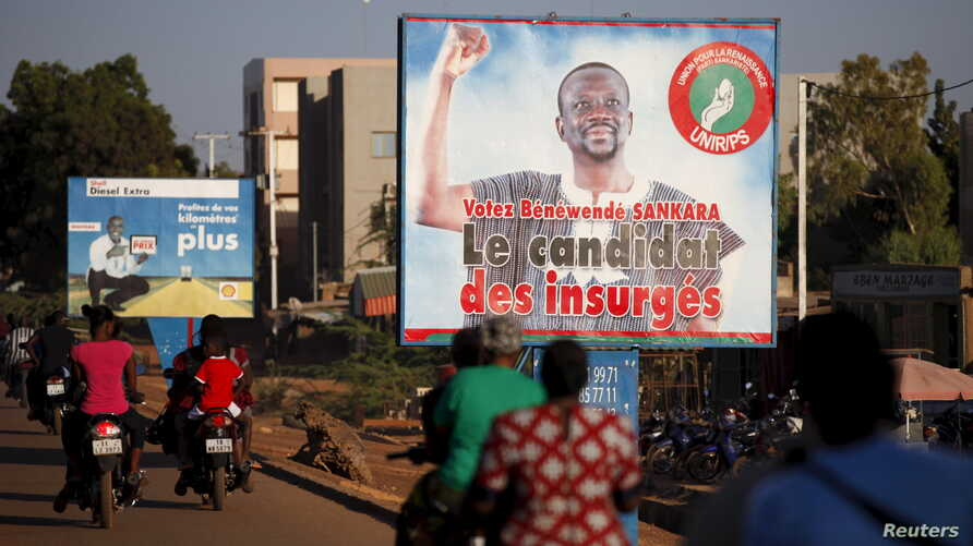 "People ride motorcycles past a billboard for presidential candidate Benewende Sankara in Ouagadougou, Burkina Faso, Nov. 28, 2015. The billboard reads, ""Vote Benewende Sankara, the insurgents' candidate."""