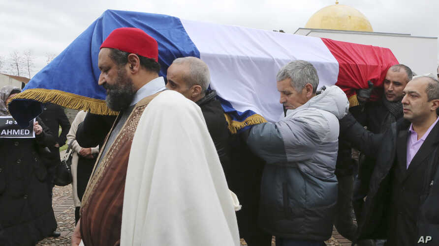 People carry the coffin of slain police officer Ahmed Merabet after a funeral service at the Bobigny Mosque, east of Paris, Jan. 13, 2015.