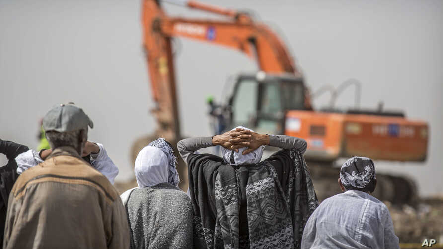 Ethiopian relatives of crash victims mourn as a mechanical digger operates at the scene where the Ethiopian Airlines Boeing 737 Max 8 crashed shortly after takeoff on Sunday killing all 157 on board, near Bishoftu, south-east of Addis Ababa, in Ethio