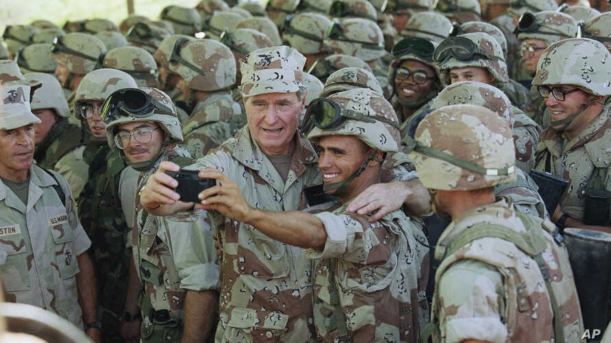 FILE - U.S. President George H. Bush holds a camera at arm's length for a self-portrait with Marines at Baidoa's airport, Jan. 1, 1993 in Baidoa.